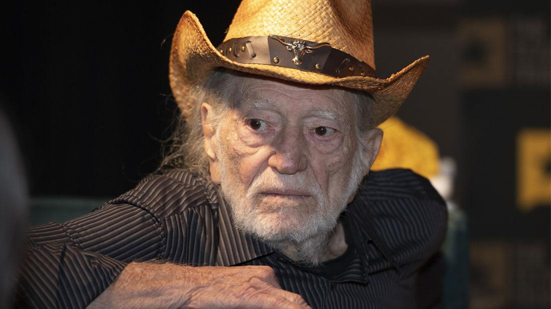 Willie Nelson Looking Left Wearing Straw Cowboy Hat and Brown Striped Shirt
